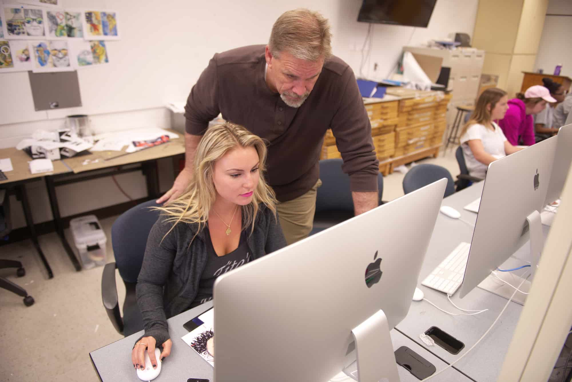 Professor Heck helping Graphic Design student in the GDES computer lab