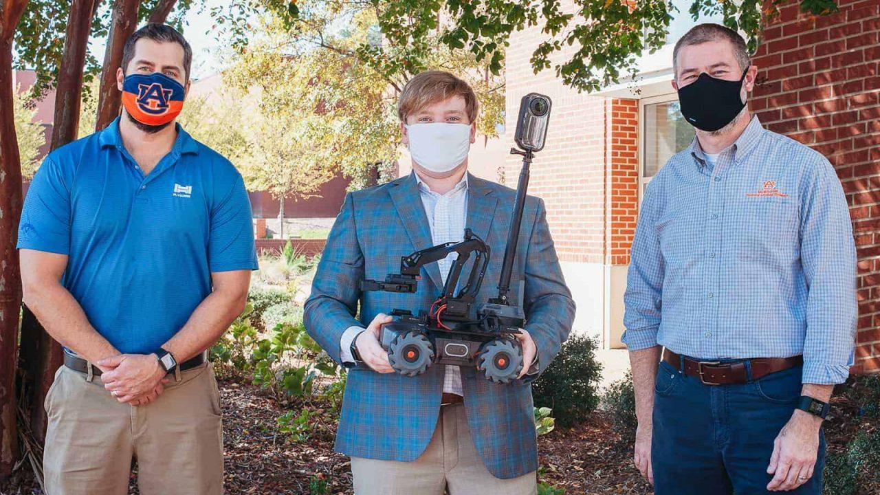 Paul Hedgepath, James Craig, and Jeff Kim pose with robot