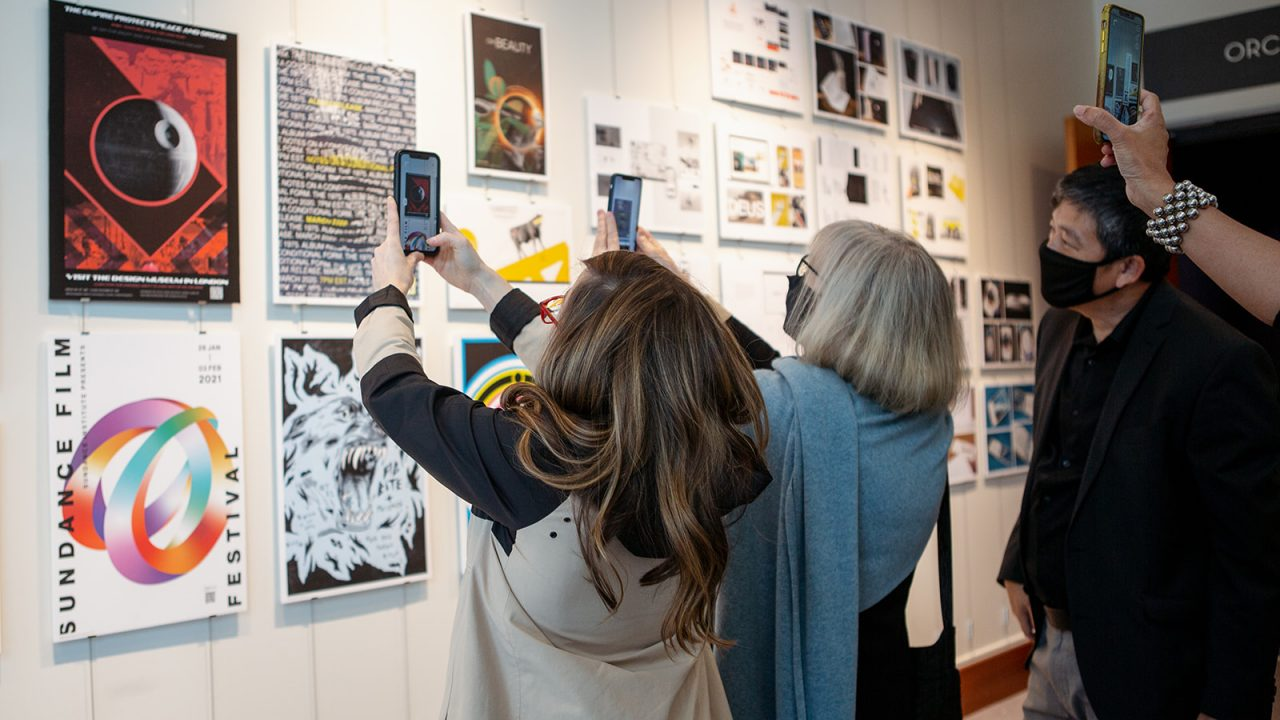 Patrons at the 2021 Graphic Design Juried Show Show interactive with digital design work using smart phones.